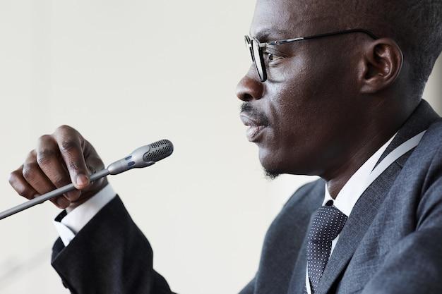 Zijaanzicht van afrikaanse zakenman spreken in microfoon op handelsconferentie
