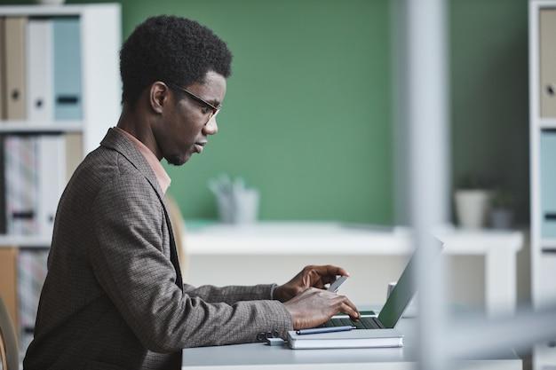 Zijaanzicht van afrikaanse zakenman zittend aan de tafel met behulp van laptop voor online betaling op kantoor