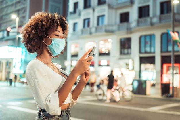 Zijaanzicht van afrovrouw met chirurgisch masker die mobiel tegen stad bij nacht gebruiken. ze draagt vrijetijdskleding. ze is in de stad.