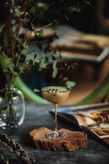 Zijaanzicht van alcoholcocktail met kiwi in een gouden glas op een houten tribune