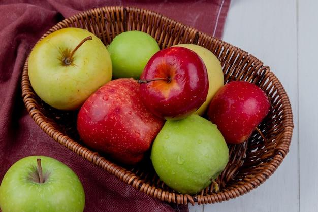 Zijaanzicht van appels in mand op bordodoek en houten