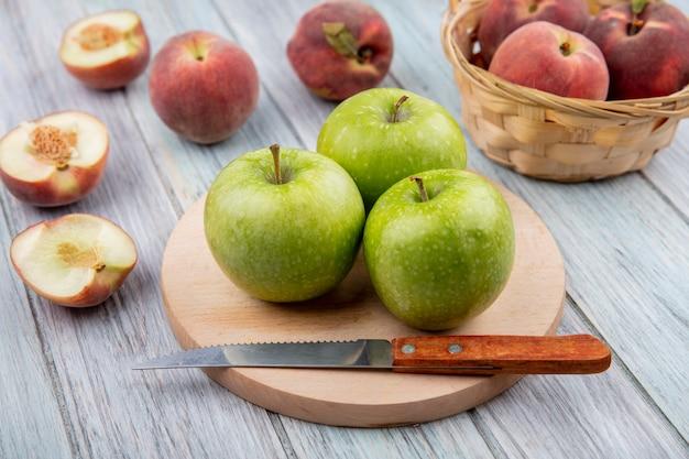 Zijaanzicht van appels op een snijplank keuken met perziken en emmer perziken op grijze ondergrond