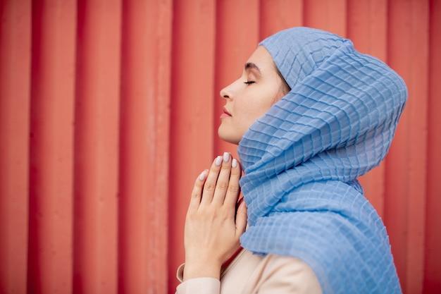 Zijaanzicht van arabische religieuze vrouw in hijab bidden met haar handen in elkaar gezet onder de kin