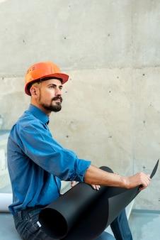 Zijaanzicht van architect met helm en blauwdrukken