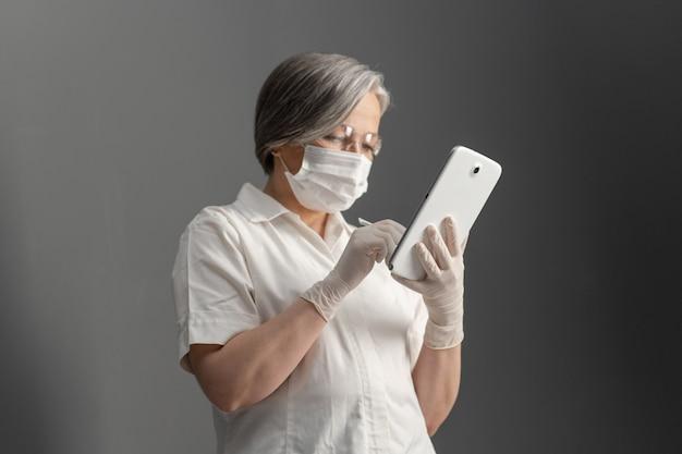 Zijaanzicht van arts die elektronische tablet gebruiken. de kaukasische oude vrouw in beschermend masker werkt met digitaal gadget bekijkend het scherm aan grijze muur