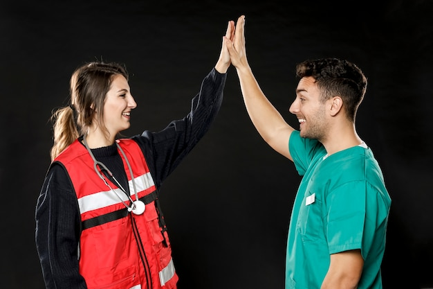 Zijaanzicht van arts en paramedicus high-fiving elkaar