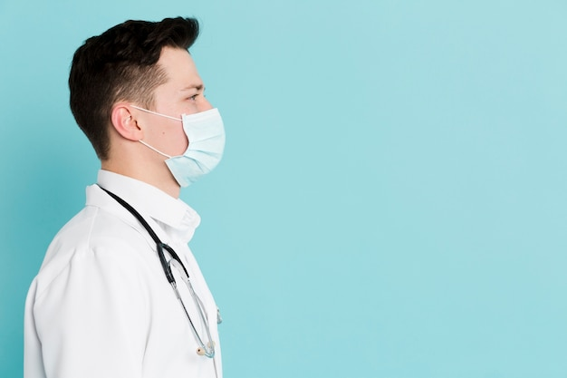 Zijaanzicht van arts met medisch masker en stethoscoop