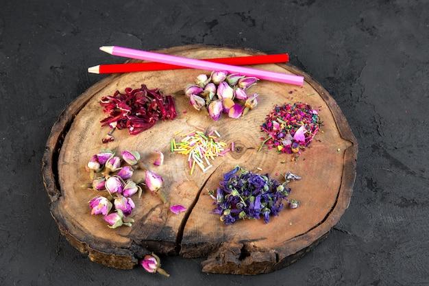 Zijaanzicht van assortiment van droge bloem en roze thee met twee potloden op houten bord op zwart