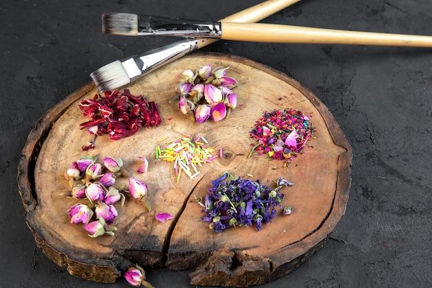 Zijaanzicht van assortiment van droge bloem en roze thee twee borstels op houten bord op zwart