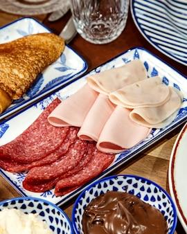 Zijaanzicht van assortiment van heerlijke vleeswaren op schotel