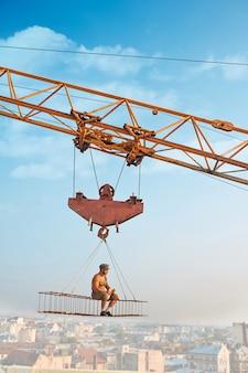 Zijaanzicht van atletische man in hoed zittend en rustend op constructie op hoog en eten. grote bouwkraan met constructie met mannetje over stad in de lucht. stadsgezicht en blauwe lucht op de achtergrond.