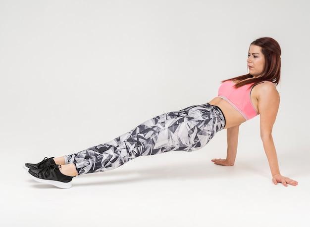 Zijaanzicht van atletische vrouw die omgekeerde opdrukoefeningen doet