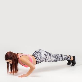 Zijaanzicht van atletische vrouw die opdrukoefeningen doet