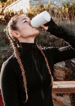 Zijaanzicht van atletische vrouw frisdrank drinken uit blikje