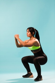 Zijaanzicht van atletische vrouw in gymnastiekuitrusting die hurkzit doen
