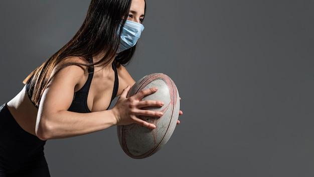 Zijaanzicht van atletische vrouwelijke rugbyspeler die bal houdt terwijl het dragen van medisch masker