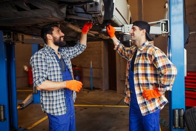 Zijaanzicht van automonteurs die bij een opgeheven auto in de garage staan
