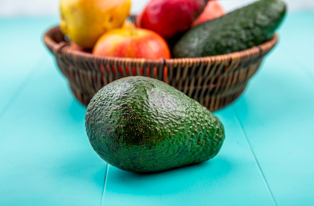 Zijaanzicht van avocado met een emmer fruit zoals granaatappelpeer op blauwe ondergrond