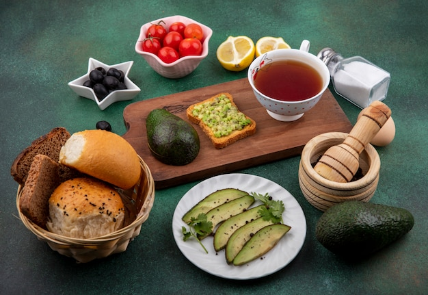 Zijaanzicht van avocado op een houten keuken bord met een kopje thee met zwarte olijven tomaten citroenen een emmer brood op groen oppervlak