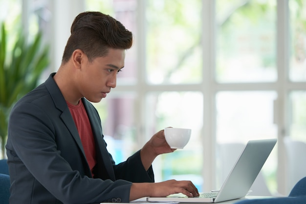 Zijaanzicht van aziatische kerel die koffie nippen en aan laptop computer werken