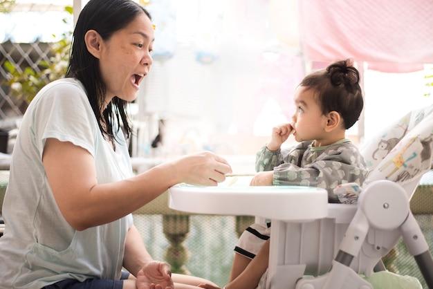 Zijaanzicht van aziatische moeder probeert haar schattige babymeisje zelf te laten eten, ze draagt een babyschort zittend op de eettafel, baby-led weaning-concept