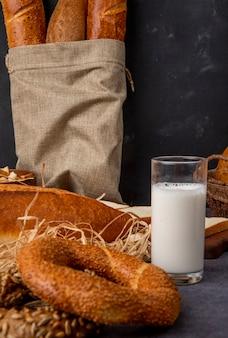 Zijaanzicht van bagel en glas melk met zak stokbrood op kastanjebruine oppervlakte en zwarte achtergrond met exemplaarruimte