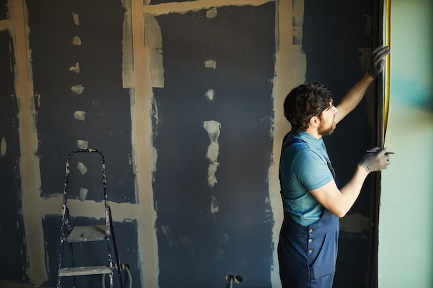 Zijaanzicht van bebaarde bouwvakker die muur met band meet tijdens het bouwen of renoveren van huis, exemplaarruimte