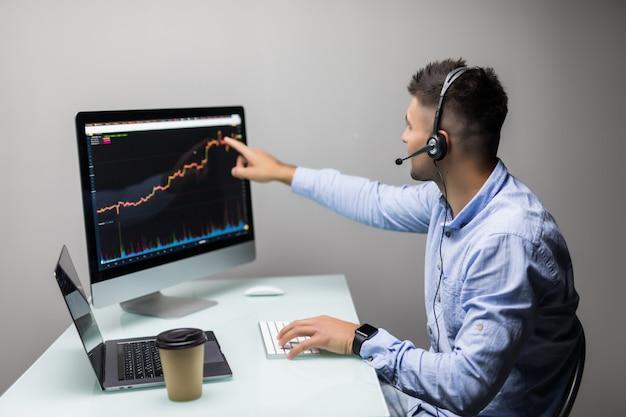 Zijaanzicht van beursmakelaar praten koptelefoon kijken naar grafieken op meerdere schermen in kantoor