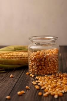 Zijaanzicht van biologische en verse maïskorrels op een glazen pot met pitten geïsoleerd op een houten muur