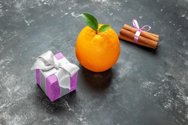 Zijaanzicht van biologische verse sinaasappel met stengel en blad in de buurt van een geschenk en kaneellimoenen op donkere achtergrond