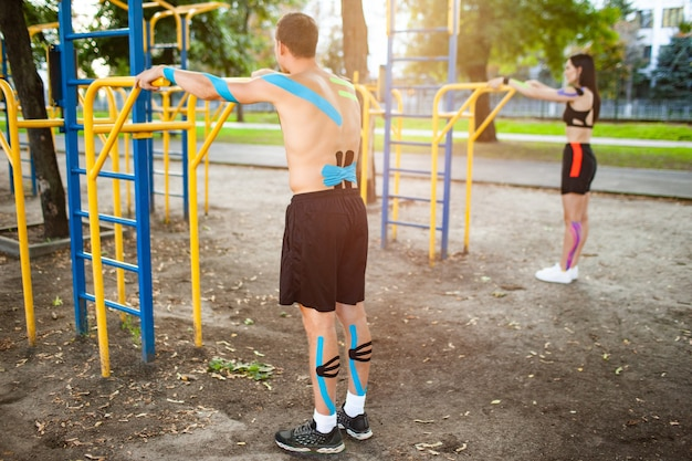 Zijaanzicht van blanke atleten koppel met kinesiologie elastische taping op lichamen, onherkenbare man en brunette vrouw training met behulp van bars op sportveld. concept van training.
