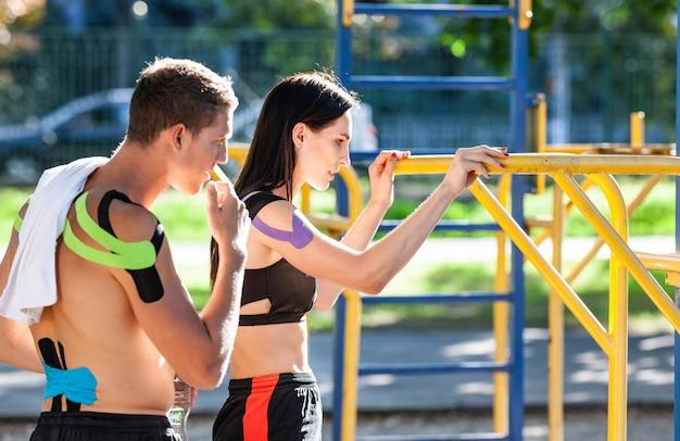 Zijaanzicht van blanke atleten met kinesiologie elastische taping op lichamen