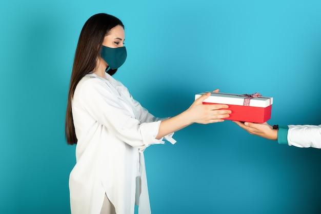 Zijaanzicht van blij vrolijk meisje in beschermend masker, cadeau ontvangen, geïsoleerd op blauwe achtergrond.