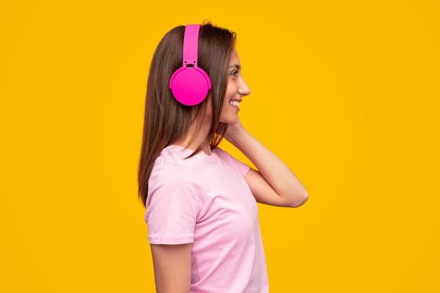 Zijaanzicht van blije jonge vrouw in roze t-shirt koptelefoon aan te raken en glimlachen terwijl u luistert naar favoriete liedje