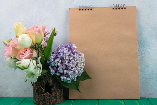 Zijaanzicht van bloemen in boomkom en notitieblok op groene oppervlakte en witte achtergrond met exemplaarruimte