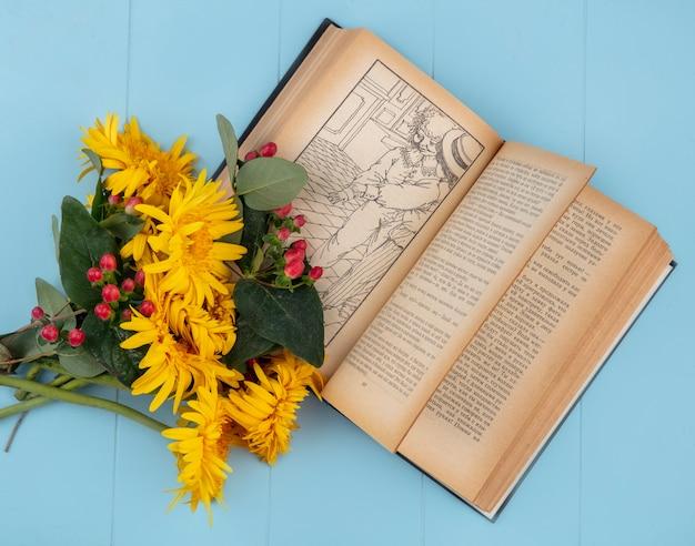 Zijaanzicht van bloemen op open boek op blauwe oppervlakte