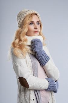 Zijaanzicht van blonde vrouw in de winterkleren die van de wamzomer dromen