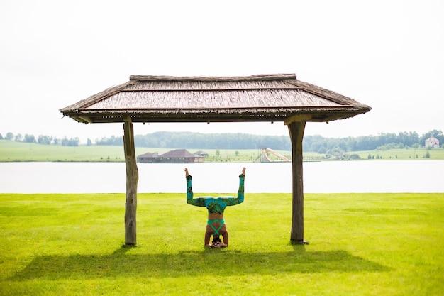 Zijaanzicht van blote voeten jonge geconcentreerde vrouw doet handstand in park in zomerdag