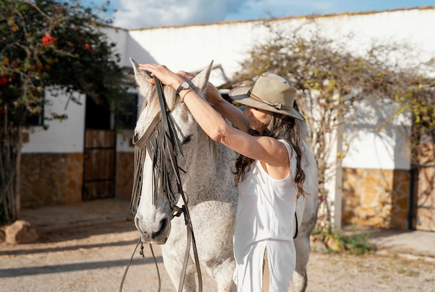 Zijaanzicht van boerin die haar paard uitrust op de boerderij