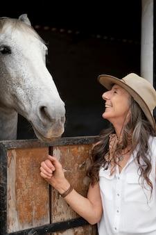 Zijaanzicht van boerin met haar paard op de boerderij