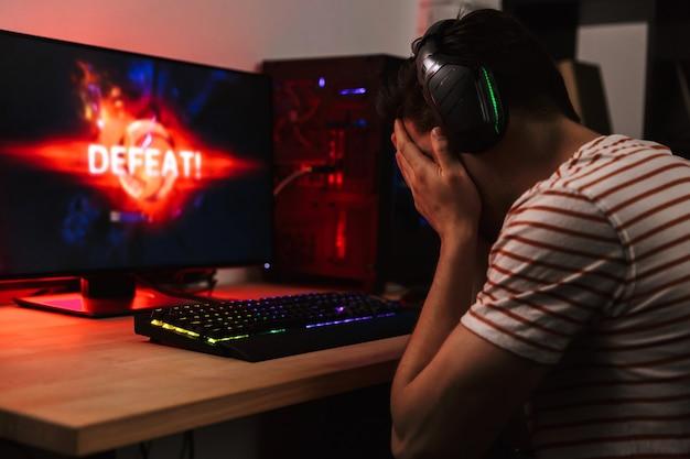 Zijaanzicht van boos gamer spelen van videospellen op computer