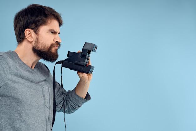 Zijaanzicht van boze mannelijke fotograaf met een professionele camera