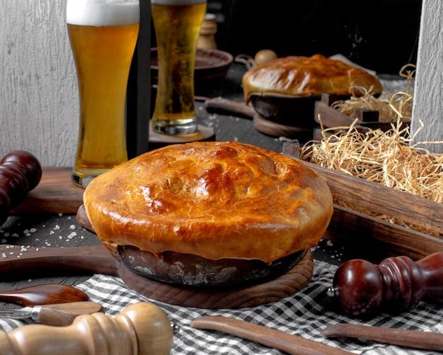 Zijaanzicht van braadpan met worstjes in een klei kom op een houten snijplank