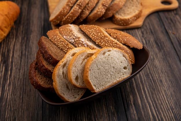 Zijaanzicht van brood als gesneden gezaaide bruine maïskolfrogge en witte in kom en op scherpe raad op houten achtergrond