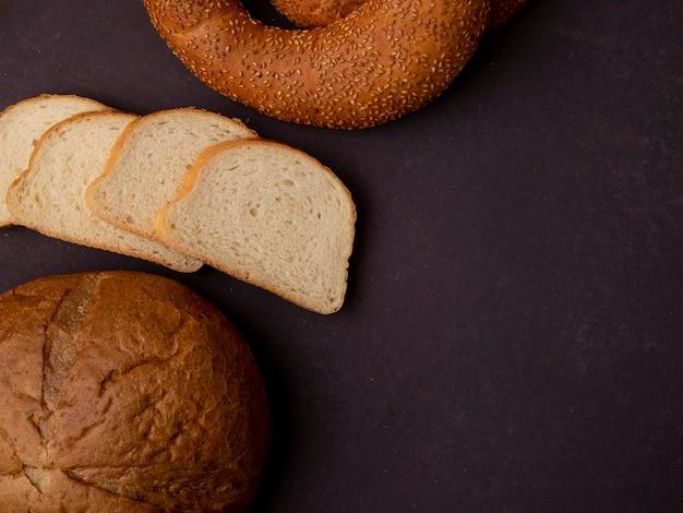 Zijaanzicht van brood als klassieke plakken van het maïskolf witte brood en ongezuurd broodje op kastanjebruine achtergrond met exemplaarruimte