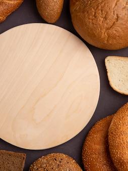 Zijaanzicht van brood als maïskolf bagel wit en roggebrood sneetjes met snijplank op kastanjebruine achtergrond