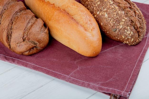 Zijaanzicht van brood als vietnamees en zwart gezaaid stokbrood en zwart brood op bordodoek en houten oppervlakte
