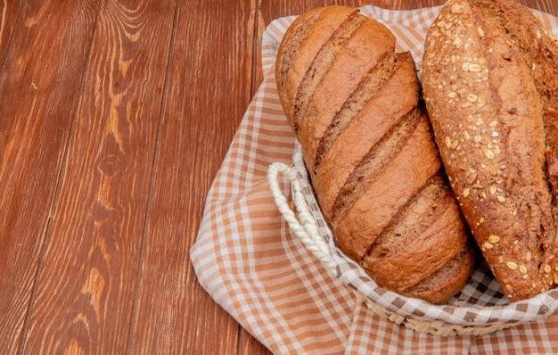 Zijaanzicht van brood als zwarte en geplaatste baguette in mand op geruite doek en houten oppervlak met kopie ruimte