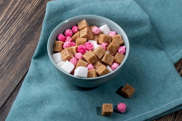 Zijaanzicht van bruine suikerklontjes met roze suikergoed in een kom op blauw