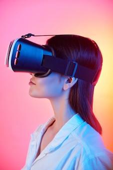 Zijaanzicht van brunette meisje in witte blouse met behulp van virtual reality-bril tegen tedere roze en gele achtergrond